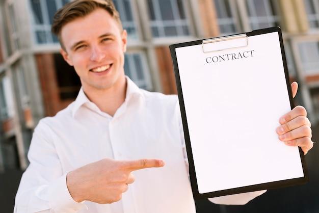 Средний выстрел счастливый человек, указывая на контракт