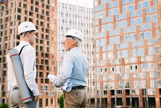 Боковой вид мужчины обсуждают архитектуру