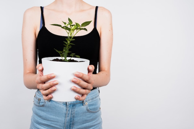 コピースペースを持つ白い植木鉢を保持している女性