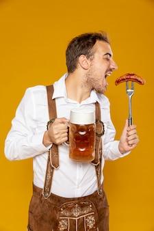 ビールパイントとソーセージを持つ男