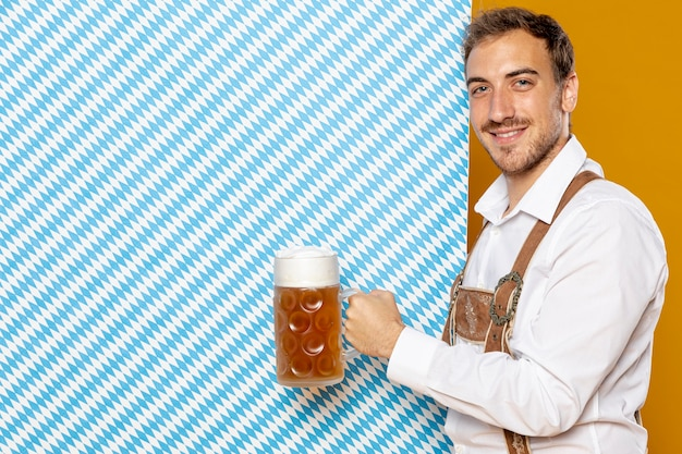 Мужчина держит пиво пинта и узорчатый фон