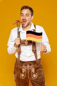 ドイツのソーセージとフラグを持つ男
