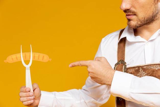 Человек, указывая на реплику немецкой колбасы