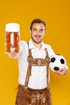 ボールとビールのパイントを抱きかかえた
