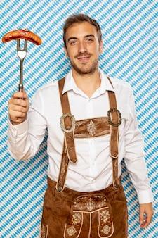 Средний снимок человека с немецкой колбасой