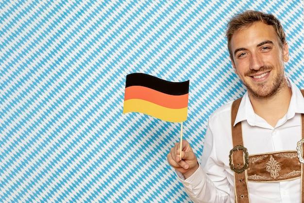 Мужчина держит немецкий флаг с копией пространства