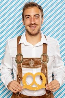 Средний снимок человека, держащего немецкий крендель