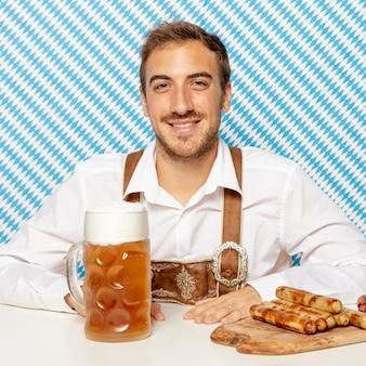 Средний снимок человека с немецкими колбасками и пивом