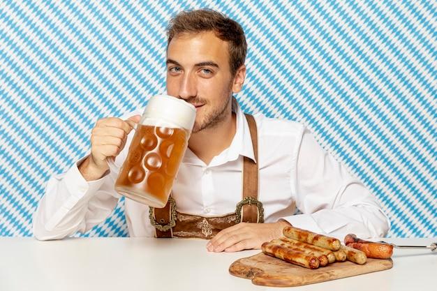Мужчина пьет светлое пиво и немецкие колбаски