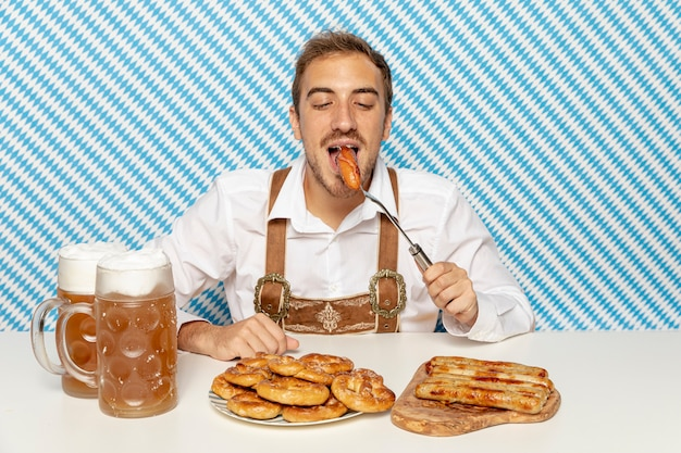 Средний снимок человека, едящего немецкие колбаски
