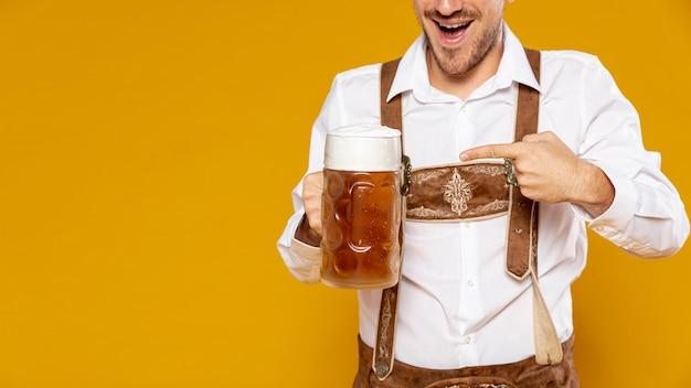 Мужчина держит пиво пинта с копией пространства