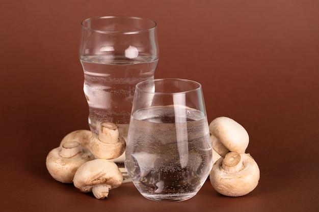 Композиция со стаканами воды и грибов