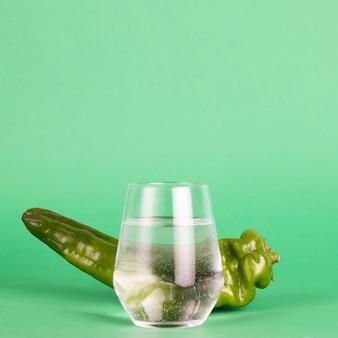 緑の背景に新鮮な唐辛子と水のガラス