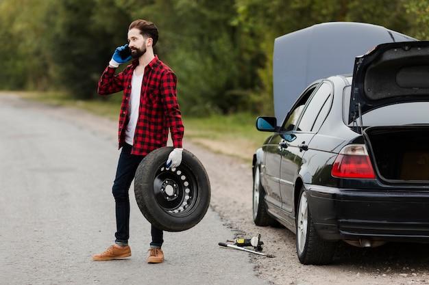 タイヤを押しながら電話で話している男性
