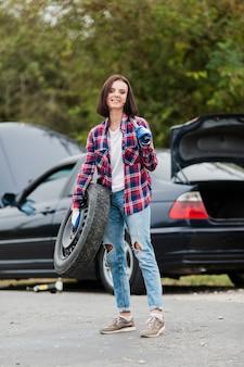タイヤとレンチを持つ女性の完全なショット