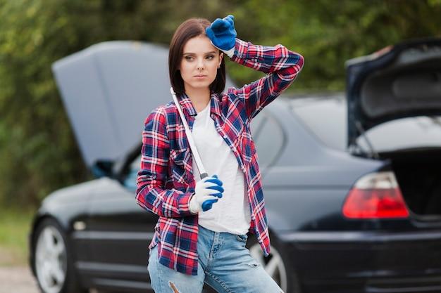 Женщина держит гаечный ключ с автомобилем в фоновом режиме