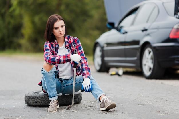 タイヤの上に座ってレンチを持つ女性