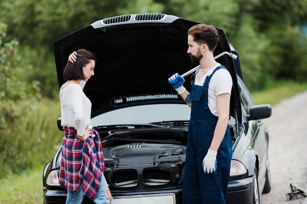 女性と開いている車のフードを持つ男