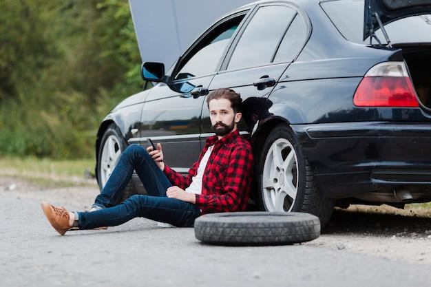 道路の上に座って、車にもたれて男