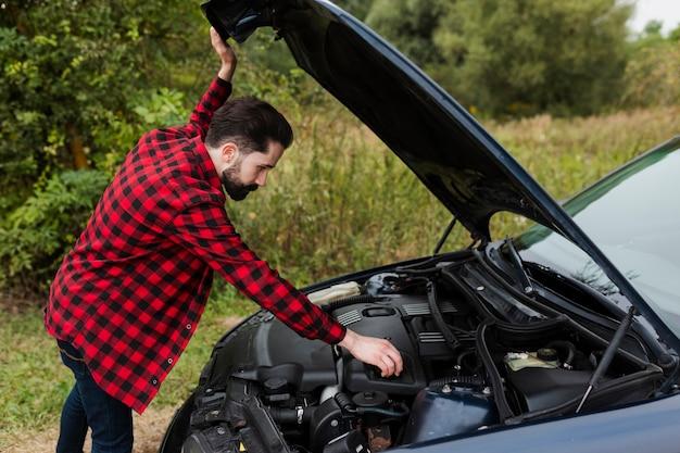 エンジンをチェックする男の側面図