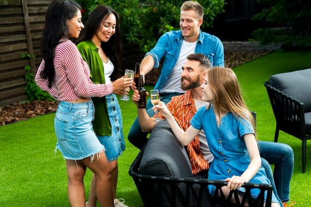 Группа друзей с напитками на открытом воздухе