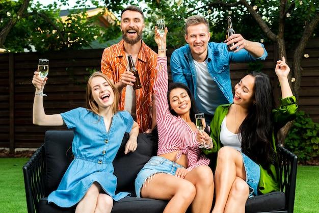 Счастливые молодые люди празднуют с напитками