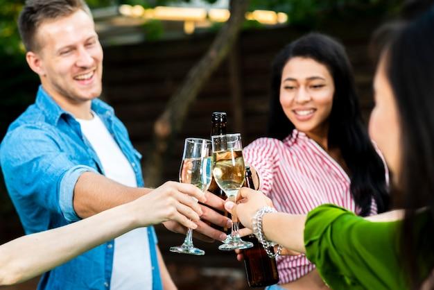 Крупным планом молодые люди, поджаривание напитков вместе