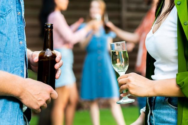 Крупным планом молодой мужчина и женщина, держащая напитки