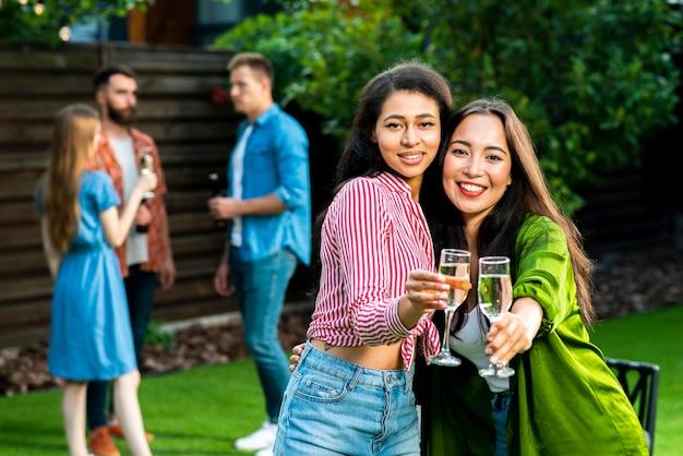 Симпатичные молодые девушки с напитками, глядя на камеру