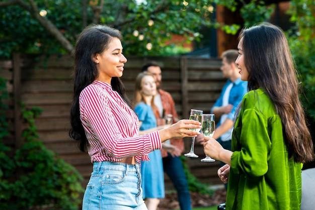 Вид спереди молодых девушек поджаривания напитков