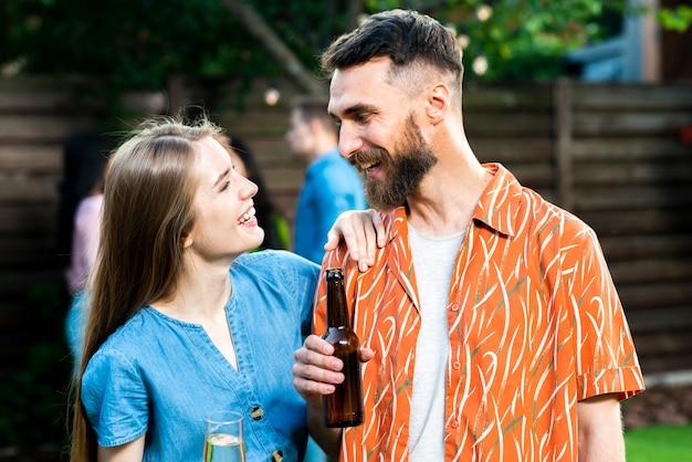 Довольно молодые друзья с напитками, глядя друг на друга
