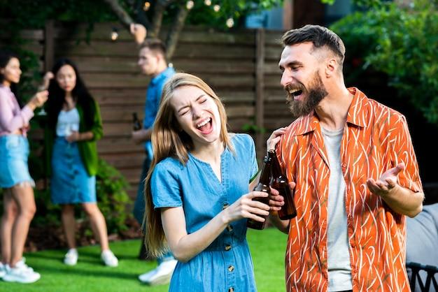 Вид спереди друзей, смеющихся с напитками