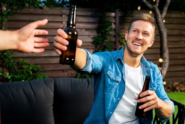 Веселый молодой человек передает пиво