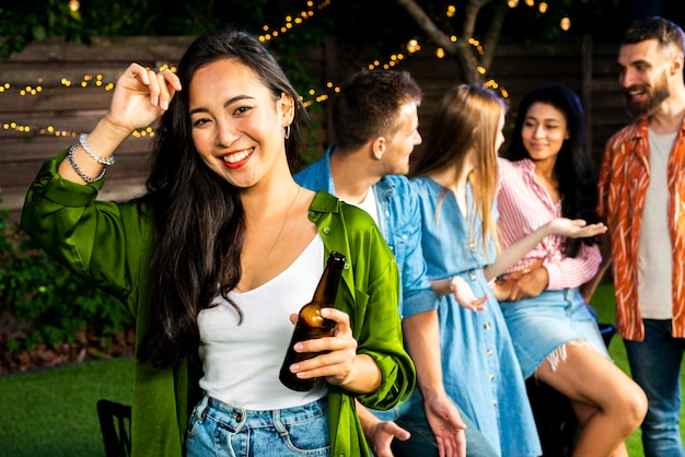 Улыбающаяся молодая девушка держит бутылку пива