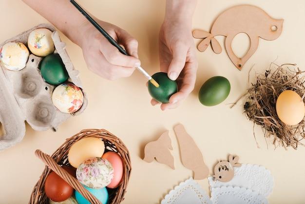 Вид сверху женщина, украшающая пасхальные яйца