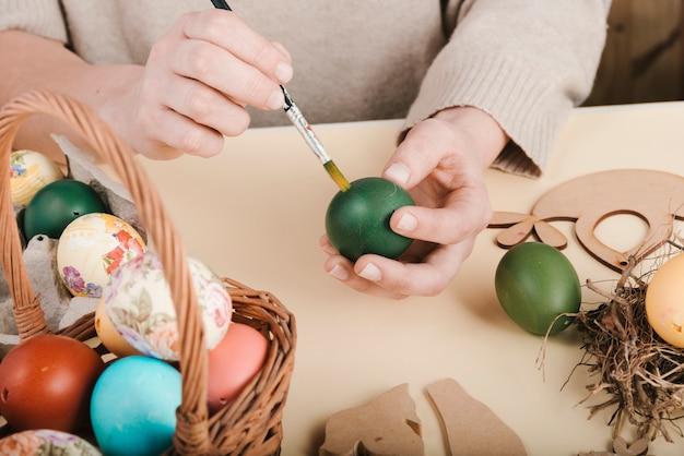 Высокий угол женщины украшают пасхальные яйца
