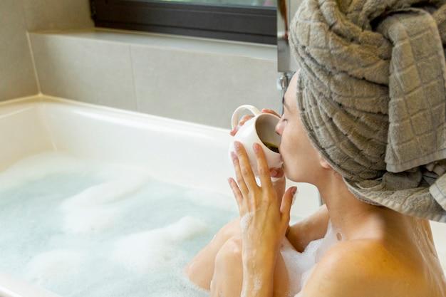バスタブでコーヒーを飲むクローズアップ女性