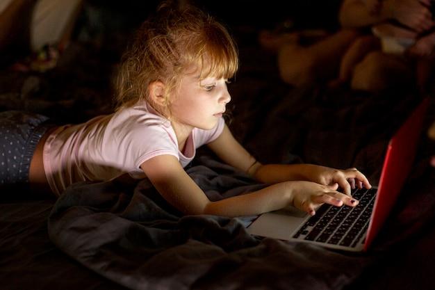 Вид сбоку девушка в постели с ноутбуком