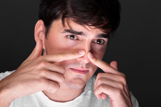 鼻に触れるクローズアップの若い男