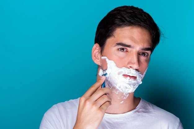 Красивый мужчина бреет бороду