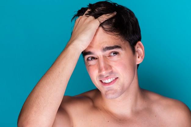 Улыбающийся молодой человек, причесывающий волосы
