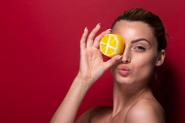 Взрослая женщина, охватывающих глаз с апельсином