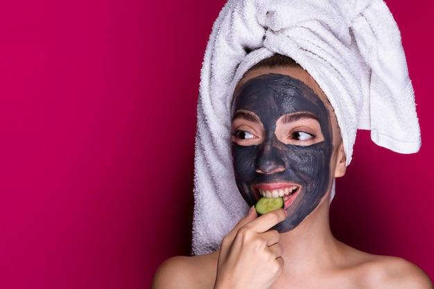 キュウリの試飲の顔のマスクを持つ女性