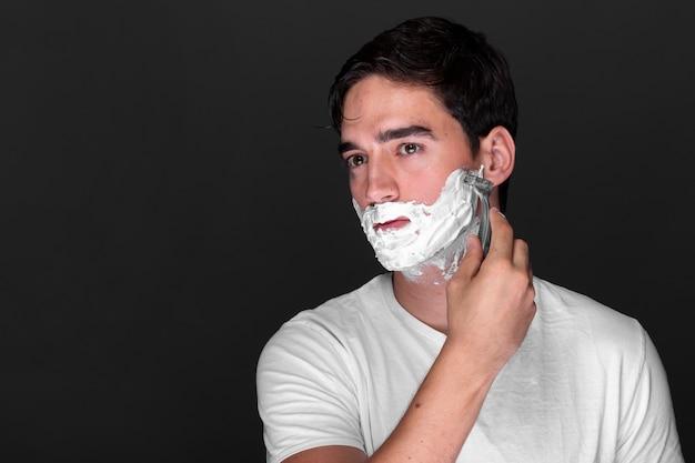 Взрослый мужчина бреет бороду