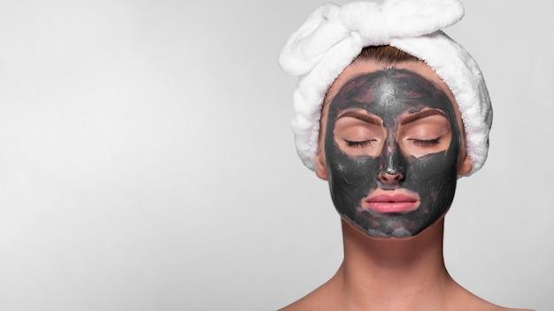 フェイスマスクを持つフロントビュー女性