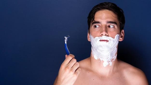 シェービングクリームとかみそりを持つ成人男性
