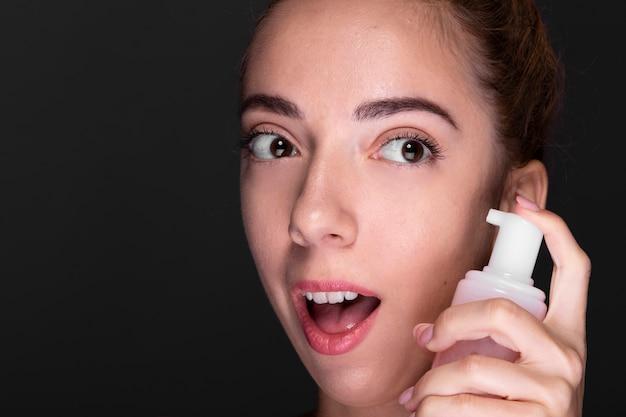 Крупным планом девушка с продуктом по уходу за кожей
