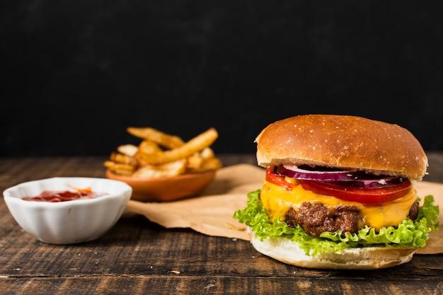黒い背景とフライドポテトとハンバーガー