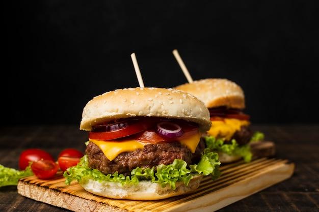 黒い背景とカットボード上のハンバーガー