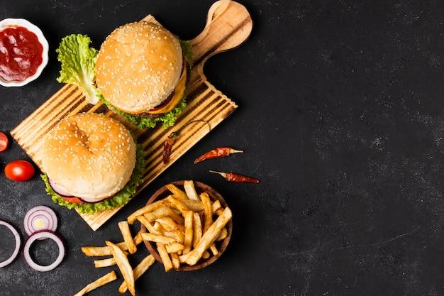 Плоская кладка гамбургеров и картофеля фри с копией пространства